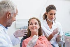 Tandarts die met patiënt spreken terwijl de verpleegster de hulpmiddelen voorbereidt Stock Afbeeldingen