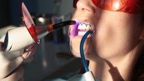 Tandarts die met tandpolymerisatielamp werken in mondholte stock footage