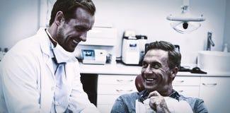 Tandarts die over digitale tablet met mannelijke patiënt bespreken royalty-vrije stock afbeelding