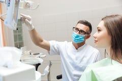 Tandarts die x ray beeld verklaren aan patiënt op HOOFDmonitor Royalty-vrije Stock Foto's