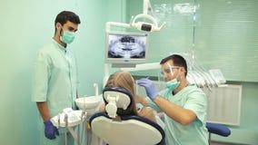 Tandarts die tand genezende UVlamp op tanden van patiënt gebruiken stock video