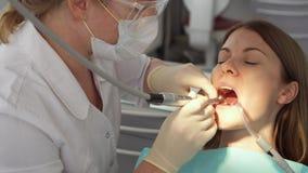 Tandarts die tanden behandelen aan vrouwenpatiënt in kliniek Vrouwelijke professionele arts op het werk Tand Controle stock videobeelden