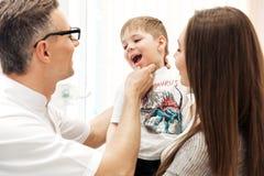 Tandarts die tanden van weinig jongen met zijn moeder het letten onderzoeken op Stock Foto