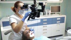 Tandarts die tandmicroscoop in tandheelkunde voor verrichting van een vrouwenpatiënt gebruiken stock video