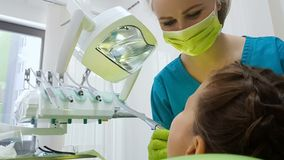 Tandarts die zorgvuldig jonge geitjestand, moderne pediatrische de stomatologiekliniek boren royalty-vrije stock afbeeldingen