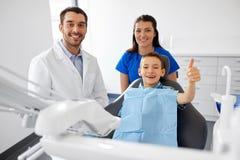 Tandarts en jongen die duimen tonen bij tandkliniek stock foto's