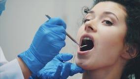 Tandarts en patiënt Jonge mooie tandarts die tanden van een mooie jonge vrouw in het bureau van de tandarts herstellen tandarts stock videobeelden
