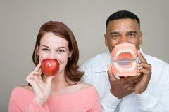 Tandarts en vrouw die een appel en een kunstgebit houden Royalty-vrije Stock Fotografie