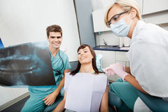 Tandarts With Female Assistant die Röntgenstraalbeeld tonen royalty-vrije stock foto's
