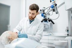 Tandarts met hogere vrouwenpatiënt in het chirurgie tandbureau royalty-vrije stock foto's