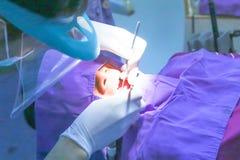 Tandarts zeer zorgvuldig controle omhoog en reparatietand van zijn jonge vrouwelijke patiënt Stock Afbeeldingen