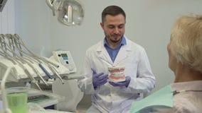 Tandartsexplaines iets op lay-out van tanden aan zijn vrouwelijke cliënt stock afbeeldingen