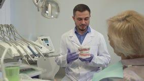 Tandartsexplaines iets op lay-out van tanden aan zijn vrouwelijke cliënt stock videobeelden