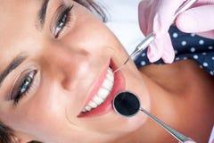 Tandartshanden die aan vrouwelijke tanden werken Stock Foto