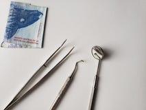 tandartswerktuigen voor mondeling overzicht en Argentijns bankbiljet van 200 peso's stock foto's
