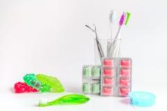 Tandborstar i exponeringsglas på vita bakgrundshjälpmedel för muntlig omsorg Arkivbild