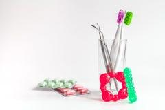 Tandborstar i exponeringsglas på vita bakgrundshjälpmedel för muntlig omsorg Royaltyfri Bild