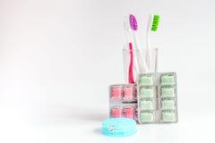 Tandborstar i exponeringsglas på vita bakgrundshjälpmedel för muntlig omsorg Royaltyfri Foto