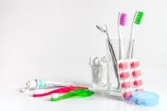 Tandborstar i exponeringsglas på vita bakgrundshjälpmedel för muntlig omsorg Royaltyfria Bilder