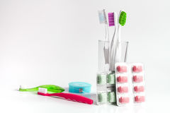 Tandborstar i exponeringsglas på vita bakgrundshjälpmedel för muntlig omsorg Royaltyfria Foton
