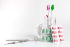 Tandborstar i exponeringsglas på vita bakgrundshjälpmedel för muntlig omsorg Arkivbilder