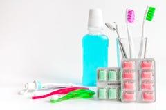 Tandborstar i exponeringsglas på vita bakgrundshjälpmedel för muntlig omsorg Royaltyfri Fotografi
