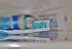 Tandborste med vitt tandkrämsammanträde på räknare-överkant royaltyfria bilder