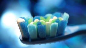 Tandbrushon en bakgrund av en abstrakt blå bokeh lager videofilmer