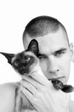 Tandem. Handsome man holding the siamese cat Royalty Free Stock Image