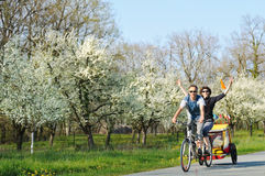 Tandem bicycle. A young couple on holiday on a country road Royalty Free Stock Image