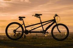 Tandem cykel i aftonen Arkivbild