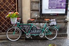 Tandem cykel som annonserar restaurangen & st?ngen f?r Na Balkany p? Warszawa den gamla stadstirrandet Miasto royaltyfri foto