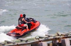 Tandem de monte de couples sur un scooter de mer rouge Images stock