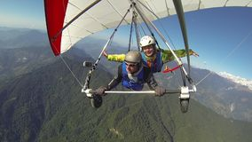 Tandem flight in a hang glider. The girl waves her hands in tandem flight on a hang glider