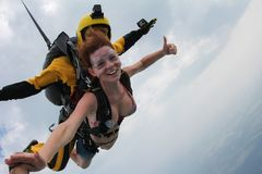 Tandem skydiving. Girl is flying in the cloudy sky. royalty free stock photography