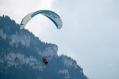 Tandem paragliders flying in the cloudy sky royalty free stock photos
