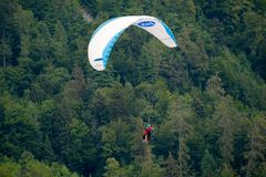 Tandem paragliders flying in the cloudy sky royalty free stock images