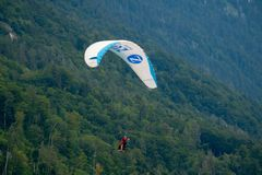 Tandem paragliders flying in the cloudy sky royalty free stock photography
