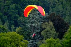 Tandem paragliders flying in the cloudy sky royalty free stock photo
