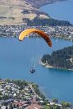 Tandem paragliding över sjön Wakatipu i Queenstown, Nya Zeeland Royaltyfri Fotografi