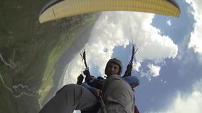 Tandem Paragliding in the Mountains. Two People are Flying on a Paraglider in the Mountains stock video