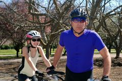 Tandem ride. Playful picture of father and daughter ready to go on a tandem ride with trees in background Stock Photography