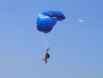 Tandem skydive. Side view of tandem skydive or parachutists in midair with blue sky background stock image