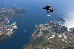Tandem skydive in freefall over blue sea. Aerial shot of the north Adriatic sea and skydiver, popular holiday spot off the coast of Vrsar, with entry to Lim Royalty Free Stock Images