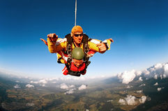 Tandem skydivers in action. Tandem skydiver in action parachuting, seen in mid air position Royalty Free Stock Image