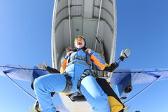 Tandem skydiving. Fun emotions at the exit moment. stock photos