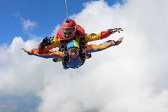 Tandem skydiving. Instructor with sexy girl. royalty free stock images