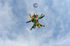 Tandem skydiving. A active girl is flying in the blue sky stock photo