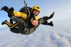 Tandem skydiving. Skydivers are flying above white clouds. Tandem instructor and tandem passenger are flying in the sky. The passenger is a girl stock photo