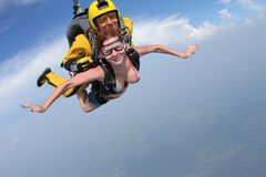 Skydiving. Girl and instructor are flying in the sky. royalty free stock photo